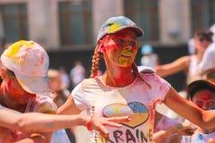 Zhytomyr, Ucrania - 25 de junio de 2016: la muchedumbre feliz de la gente que va de fiesta debajo de la nube colorida del polvo f Fotos de archivo libres de regalías