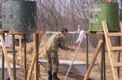 Zhytomyr, Ucrania - 5 de marzo de 2015: Los soldados en un alto limpian las armas, llenan la munición Fotografía de archivo libre de regalías
