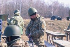 Zhytomyr, Ucrania - 5 de marzo de 2015: Los soldados en un alto limpian las armas, llenan la munición Imagen de archivo libre de regalías