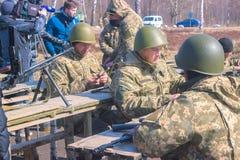 Zhytomyr, Ucrania - 5 de marzo de 2015: Los soldados en un alto limpian las armas, llenan la munición Foto de archivo