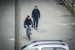 Zhytomyr, Ucrania - 19 de octubre de 2015: Bici que rueda del hombre joven en hombre que camina cercano de la ciudad Imagen de archivo