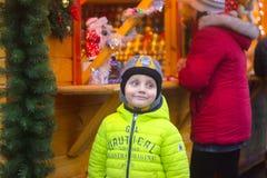 Zhytomyr, Ucrania - 10 de septiembre de 2014: Muchacho lindo muy feliz con los regalos de Navidad en fondo de madera Imágenes de archivo libres de regalías