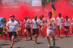 Zhytomyr Ukraina, Czerwiec, - 25, 2016: szczęśliwi ludzie tłumu bawi się pod kolorową proszek chmurą biegają rywalizację przy hol Obraz Stock