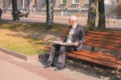 Zhytomyr Ukraina - September 05, 2015: läsning för hög man på en bänk Arkivfoton