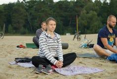 Zhytomyr, Ukraine - August 9, 2015: People practicing yoga at sunrise stock image