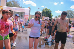 Zhytomyr, Ukraine - June 25, 2016: happy people crowd partying under colorful powder cloud run competition at holi fest. Zhytomyr, Ukraine - June 25, 2016: happy stock photo