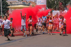 Zhytomyr, Ukraine - June 25, 2016: happy people crowd partying under colorful powder cloud run competition at holi fest. Zhytomyr, Ukraine - June 25, 2016: happy royalty free stock image