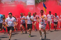 Zhytomyr, Ukraine - June 25, 2016: happy people crowd partying under colorful powder cloud run competition at holi fest. Zhytomyr, Ukraine - June 25, 2016: happy stock image
