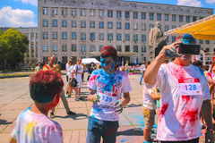 Zhytomyr, Ukraine - June 25, 2016: happy people crowd partying under colorful powder cloud run competition at holi fest. Zhytomyr, Ukraine - June 25, 2016: happy stock photography
