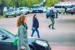 Zhytomyr, Ukraine - MAY 6, 2017: Young people is crossing the road in wrong place. Zhytomyr, Ukraine - MAY 6, 2017: Four young people is crossing the road in royalty free stock photo
