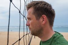 Zich dichtbij het netto volleyball bevinden en portret die van de Kaukasische mens opzij wachtend op begin van spel kijken Royalty-vrije Stock Foto
