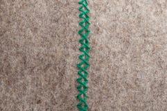 Zick zack. Close up of green hand stitch zick zack on gray woolen felt, vertical Stock Photo