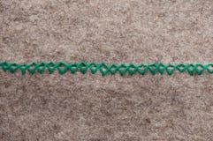 Zick zack horizontal. Close up of green hand stitch zick zack on gray woolen felt, horizontal Royalty Free Stock Photo