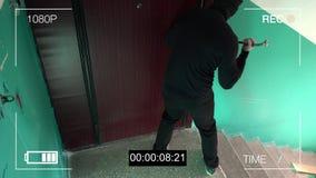Zie kabeltelevisie als inbreker die binnen door de deur met een koevoet breken stock videobeelden
