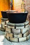 Ziegelsteinöfen mit alten Töpfen in der Küche Lizenzfreies Stockfoto