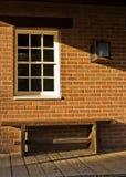 Ziegelstein, Bank und ein Fenster Stockfotografie