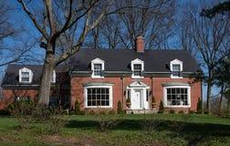Ziegelstein-Cape Cod-Haus mit Einfügungs-Mansardenfenstern Lizenzfreies Stockbild