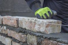 Ziegelstein installierend, errichten Sie eine Backsteinmauer 2 Lizenzfreie Stockfotos