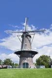 Ziegelsteinbodenmühle auf einem grünen Gebiet mit einem blauen Himmel und drastischen Wolken Lizenzfreie Stockbilder