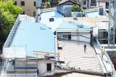Ziegelsteine, die draußen legen Baumannschaft, die an dem Dach sheetin arbeitet stockbilder