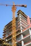 Ziegelsteine, die draußen legen Kran und hohes Gebäude im Bau Stockfoto