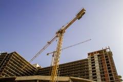Ziegelsteine, die draußen legen Neues Gebäude Gelber Turmkran gegen blauen Himmel Stockfotografie