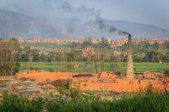 Ziegelsteinfabrik mit Kamin und schwarzem Rauche Stockfoto