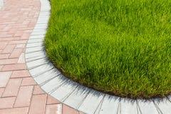 Ziegelsteingehweg und grünes Gras Lizenzfreies Stockfoto