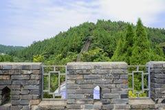 Ziegelsteingeländer der alten Wand auf Bergabhang im sonnigen Sommer Stockbild
