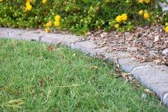 Ziegelsteingrenze entlang Grasyard Stockbilder