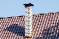 Ziegelsteinkamin auf dem Dach Stockbild