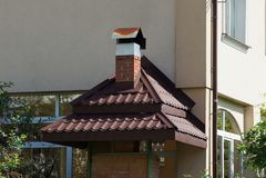 Ziegelsteinkamin mit braunen Fliesen auf einer grauen Wand eines Hauses stockfoto