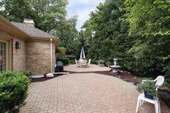 Ziegelsteinpatio mit Felsengarten stockbild