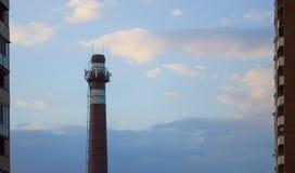 Ziegelsteinrohr des Kesselhauses auf blauem Himmel zwischen hohen Gebäuden lizenzfreie stockfotografie