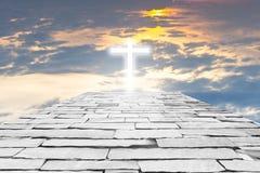 Ziegelsteinstraße zu einem transparenten Kreuz, das heraus himmlisches Licht auf t gibt Stockbilder