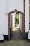 Ziegelsteintorbogen in der Wand, die führt, um im Garten zu arbeiten Stockbilder