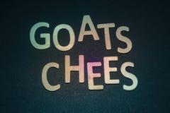 Ziegen Chees geschrieben mit bunten hölzernen Buchstaben auf ein blaues backg Lizenzfreies Stockfoto