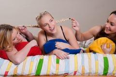 Ziehen unseres Freundinhaares an der Pyjamaparty Stockfoto
