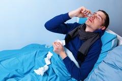 Ziek donkerbruin mannetje die neusnevel gebruiken terwijl het liggen in bed stock fotografie
