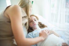 Ziek jong geitje met zuurstofmasker die in bed bij het ziekenhuis en moeder ` leggen royalty-vrije stock afbeelding
