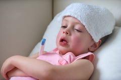 Ziek kind die met hoge koorts in bed leggen stock foto