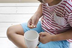 Ziek kind die pillen met houten witte achtergrond eten Hoogste mening Stock Afbeelding