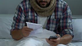 Ziek mannetje die tot pillen online in smartphone opdracht geven, zoekend informatie, zittend bed stock videobeelden