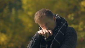 Ziek mannetje in sjaal die en in de herfstpark hoesten niezen, gevangen koude, besmetting stock video