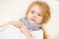 Ziek meisje die in het bed liggen Stock Foto