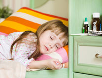 Ziek meisje die op een bed liggen stock afbeelding