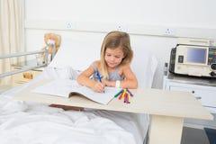 Ziek meisjes kleurend boek in het ziekenhuis Stock Fotografie