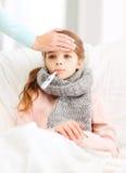 Ziek meisjeskind met thermometer en gevende moeder stock afbeelding