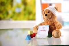 Ziek Teddy Bear met Medische Kaart en Vormblokken Stock Foto