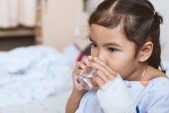 Zieke Aziaat weinig hand van het kindmeisje drinkt zoet water stock afbeelding
